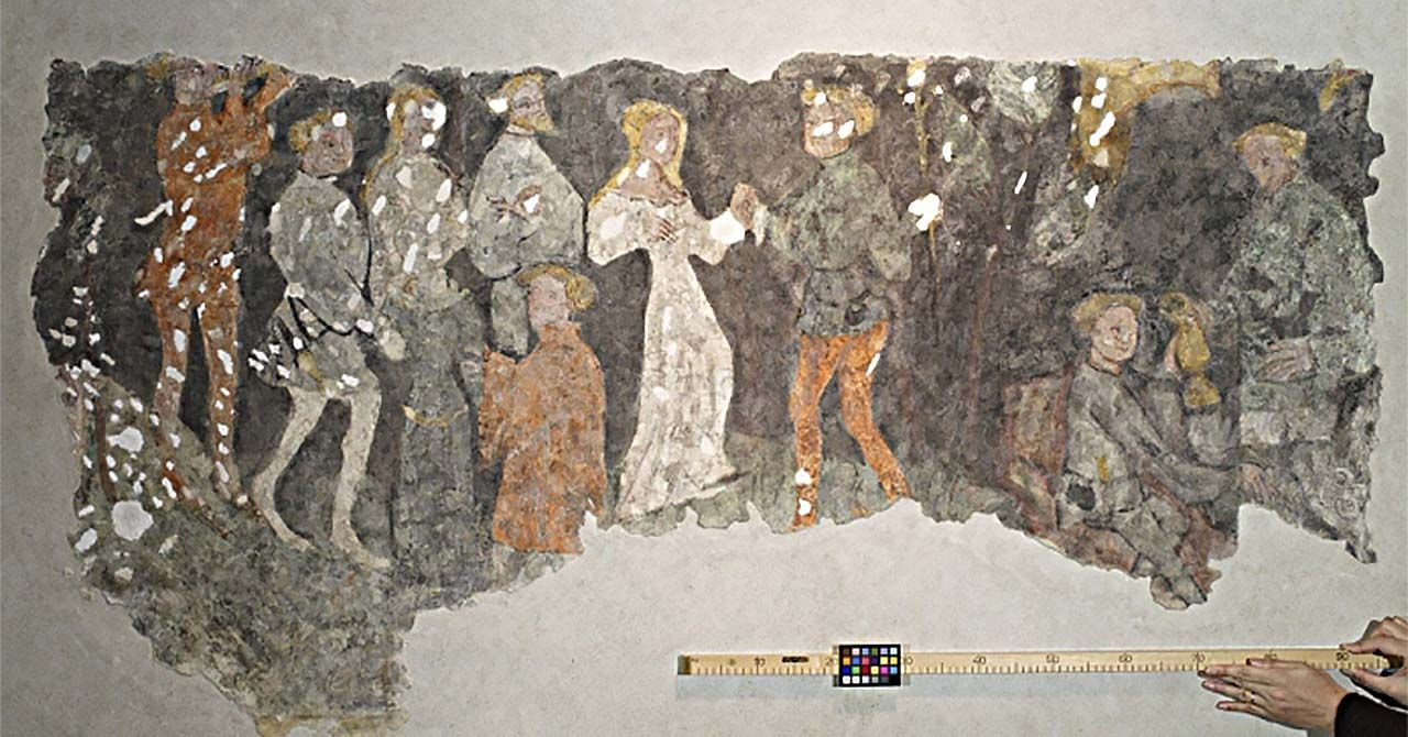 Large section of a fresco showing a group of people, around a man and woman in the center holding hands. A person is holding up a yard stick underneath the fresco. The yardstick has a small color-matching grid attached to it.
