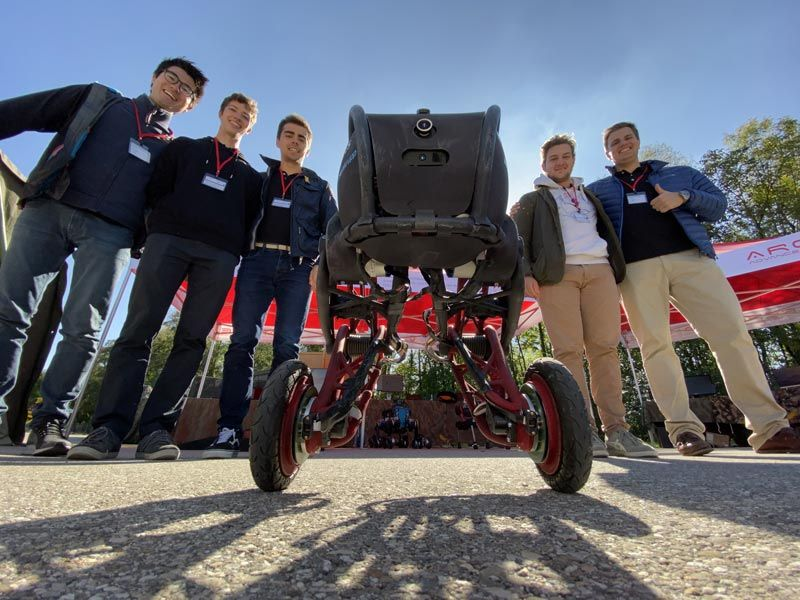 Five smiling members of the Ascento team standing outside and gathered around the robot. One member giving the thumbs-up.