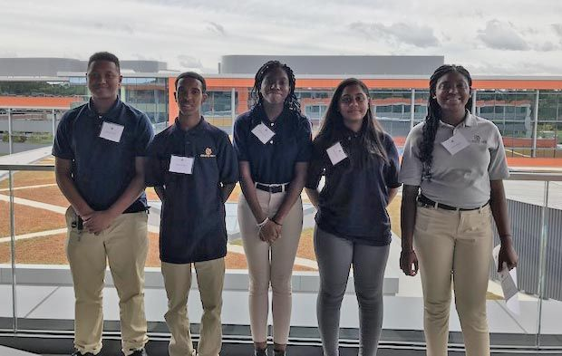 The five Cristo Rey students standing on a balcony at MathWorks. Behind them is the company campus including other MathWorks buildings.