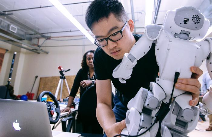 Graduate student Jin Xu sets up the NAO in the lab. A cable connects the robot to the laptop.